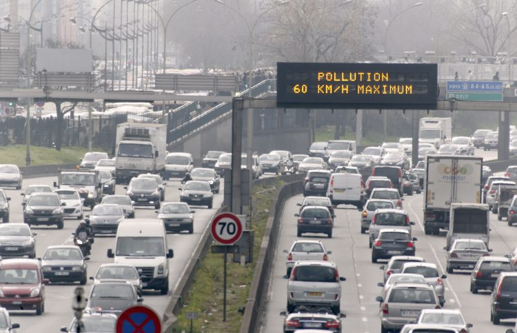 "Vehicles drive past an information board asking to limit their speed to 60km/h on the ring road on March 15, 2014 in Paris. Overall, more than 30 departments in France were hit by maximum level pollution alerts, prompting Ecology Minister Philippe Martin to say air quality was ""an emergency and a priority for the government"". AFP PHOTO / FRANCOIS GUILLOT"